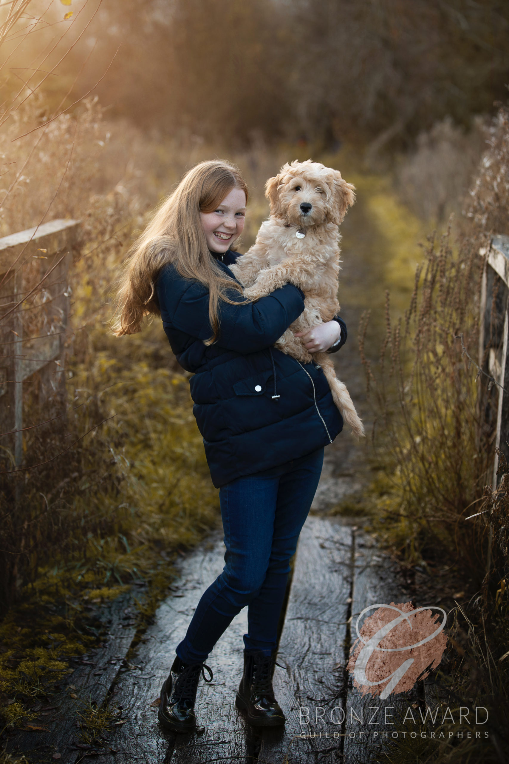 Sarah Dutton Photography was awarded this Bronze award for capturing a beautiful image of a young girl and her pet Dog. The golden hour sunlight is capturing her hair and they are both looking at me with a beautiful smile on the girls face.