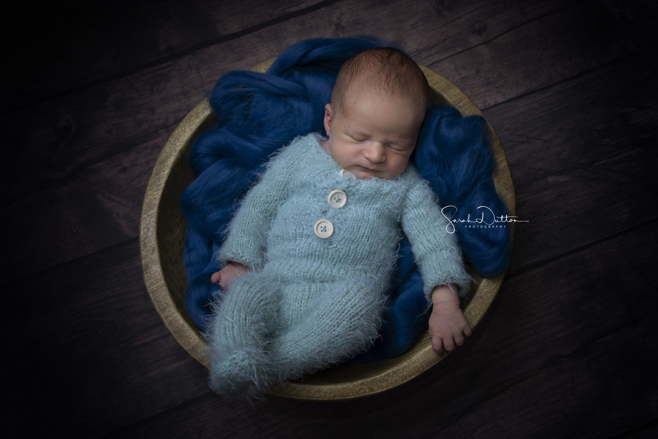 Newborn baby in a blue knitted romper taken in a studio by a photographer in Whitchurch Hampshire